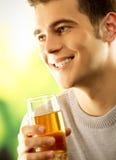 Hombre con el vidrio de zumo de fruta Imagenes de archivo