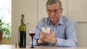 Hombre con el vino de consumición del smartphone almacen de metraje de vídeo