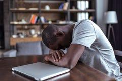 Hombre con exceso de trabajo que duerme cerca del ordenador portátil Fotos de archivo