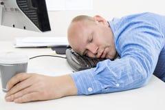 Hombre con exceso de trabajo y cansado en la oficina Imagenes de archivo