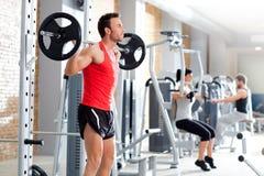 Hombre con gimnasia del equipo de entrenamiento del peso de la pesa de gimnasia foto de archivo libre de regalías