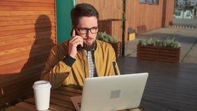 Hombre con hablar al aire libre del ordenador portátil en el teléfono almacen de metraje de vídeo
