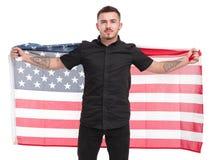 Hombre con la bandera americana en sus manos detrás el suyo detrás aisladas en el fondo blanco Fotos de archivo libres de regalías