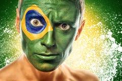 Hombre con la bandera del Brasil pintada en cara Foto de archivo