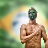 Hombre con la bandera del Brasil pintada en cara Imagenes de archivo