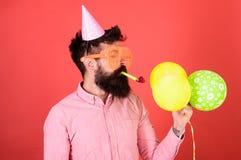 Hombre con la barba arreglada que lleva la camisa y el casquillo rosados del partido en fondo rojo Silbido del partido del hombre Foto de archivo