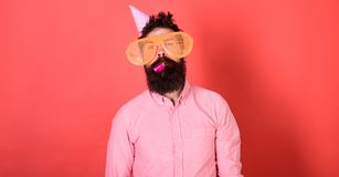 Hombre con la barba en cara tranquila con el cuerno del partido, fondo rojo El individuo en sombrero del partido con cualidades d Fotografía de archivo