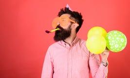 Hombre con la barba larga en fondo rojo Hombre barbudo en vidrios enormes con el silbido del partido, concepto de la celebración  Fotos de archivo libres de regalías