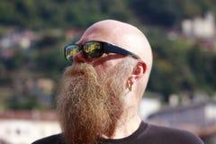Hombre con la barba larga, miradas de las gafas de sol cuidadosamente imagen de archivo