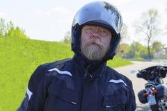Hombre con la barba, los vidrios y el casco largos de la moto, soportes en la orilla del Rin fotografía de archivo