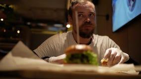 Hombre con la barba que come la hamburguesa cheeseburger almacen de metraje de vídeo