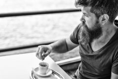 Hombre con la barba y bigote y taza de caf? Individuo barbudo que se relaja en la terraza del caf? Concepto del descanso para tom fotografía de archivo libre de regalías