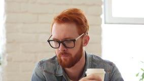 Hombre con la barba y los pelos rojos que bebe el café, té en la oficina, retrato