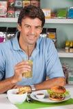 Hombre con la bebida y hamburguesa en supermercado Foto de archivo libre de regalías