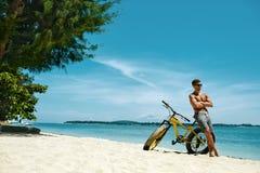 Hombre con la bici de la arena en la playa que disfruta de vacaciones del viaje del verano Foto de archivo libre de regalías
