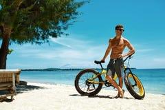 Hombre con la bici de la arena en la playa que disfruta de vacaciones del viaje del verano Imagen de archivo libre de regalías
