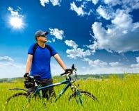 Hombre con la bici en campo verde fotografía de archivo libre de regalías