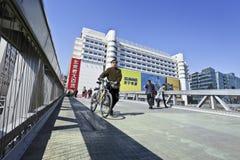 Hombre con la bici en el puente peatonal en el área de Pekín Xidan Foto de archivo libre de regalías