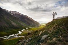 Hombre con la bici en la montaña fotos de archivo