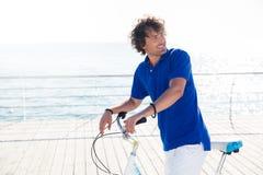 Hombre con la bicicleta que parece ausente al aire libre Fotografía de archivo
