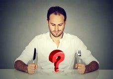 Hombre con la bifurcación y cuchillo que se sienta en la tabla que mira la placa con la pregunta roja grande imagenes de archivo