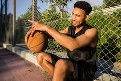 Hombre con la bola en la cancha de básquet jugador en una cancha de básquet Imagen de archivo libre de regalías