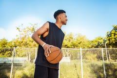 Hombre con la bola en la cancha de básquet jugador en una cancha de básquet Imágenes de archivo libres de regalías