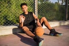 Hombre con la bola en la cancha de básquet jugador que mira a la cámara en una cancha de básquet Fotografía de archivo libre de regalías