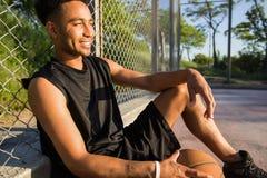 Hombre con la bola en la cancha de básquet jugador que mira a la cámara en una cancha de básquet Imágenes de archivo libres de regalías
