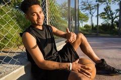 Hombre con la bola en la cancha de básquet jugador que mira a la cámara en una cancha de básquet Imagen de archivo libre de regalías