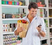 Hombre con la bolsa de papel usando el teléfono móvil adentro Foto de archivo
