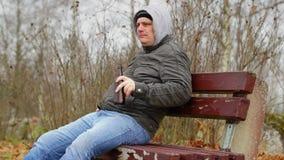 Hombre con la botella de cerveza en el banco en otoño