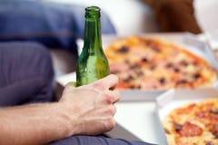 Hombre con la botella y la pizza de cerveza en casa Imágenes de archivo libres de regalías