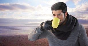 Hombre con la bufanda que bebe de la taza por el mar Fotografía de archivo libre de regalías