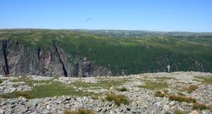 Hombre con la cámara en el borde del acantilado Fotos de archivo