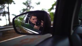 Hombre con la cámara en la reflexión de espejo de coche de un coche móvil a lo largo del camino de niebla del otoño durante viaje metrajes