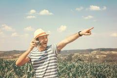 Hombre con la cámara vieja que señala con el finger Fotografía de archivo