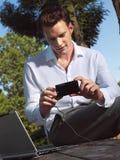 Hombre con la cámara y el ordenador portátil e Imagen de archivo