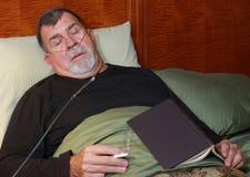 Hombre con la cánula del oxígeno que fuma en cama Fotos de archivo