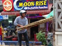 Hombre con la caña de azúcar en las calles muy transitadas de Phnom Penh - capital de Camboya Fotos de archivo libres de regalías