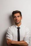 Hombre con la camisa y lazo que se inclina contra una pared con los brazos cruzados Fotografía de archivo