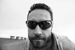 Hombre con la cara, la barba y el bigote sin afeitar en lentes de sol negros Foto de archivo
