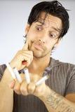 Hombre con la cara divertida de los cigarrillos Fotografía de archivo libre de regalías