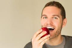 Hombre con la cara divertida que mira una manzana Fotos de archivo libres de regalías