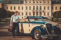 Hombre con la cartera cerca del convertible clásico Imagen de archivo