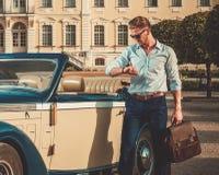 Hombre con la cartera cerca del convertible clásico Imagen de archivo libre de regalías
