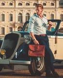 Hombre con la cartera cerca del convertible clásico Imagenes de archivo