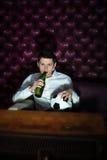 Hombre con la cerveza y bola del fútbol que ven la TV Imagen de archivo libre de regalías