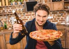 Hombre con la cerveza y la pizza Foto de archivo libre de regalías