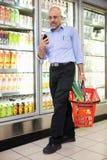 Hombre con la cesta de la tienda de comestibles y el teléfono móvil Imágenes de archivo libres de regalías